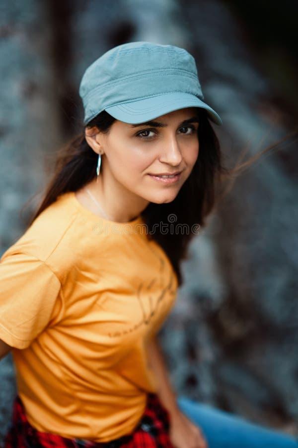 Νέο κορίτσι που φορά την κίτρινη μπλούζα και την μπλε ΚΑΠ Υπαίθρια πορτρέτο τρόπου ζωής στοκ εικόνα