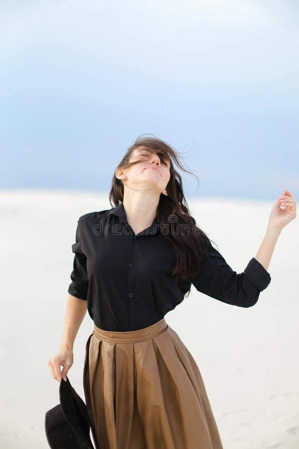 Νέο κορίτσι που φορά τη μαύρη μπλούζα και την καφετιά φούστα που στέκονται στο άσπρο υπόβαθρο και που κρατούν το καπέλο στοκ φωτογραφία με δικαίωμα ελεύθερης χρήσης