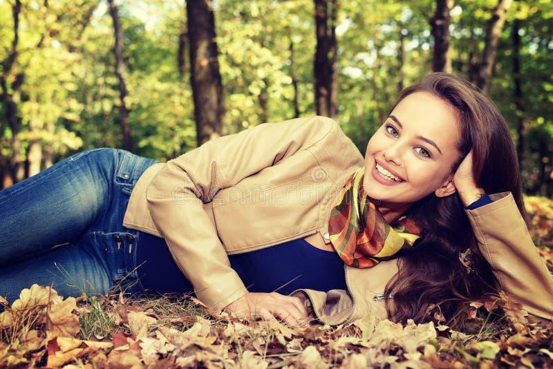 Νέο κορίτσι που χαμογελά το φθινόπωρο με τα φύλλα στοκ εικόνες