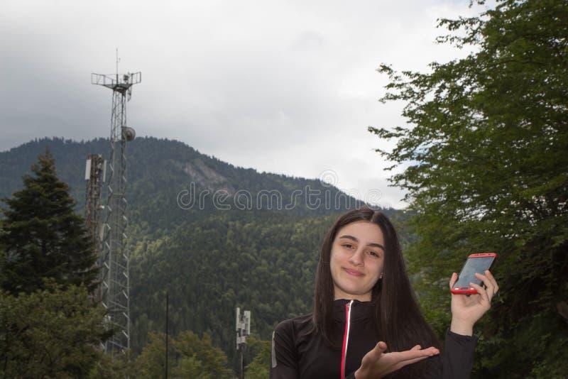 Νέο κορίτσι που χρησιμοποιεί το κινητό τηλέφωνο με τους πύργους τηλεπικοινωνιών με τις κεραίες TV και το δορυφορικό πιάτο Η έννοι στοκ φωτογραφία με δικαίωμα ελεύθερης χρήσης