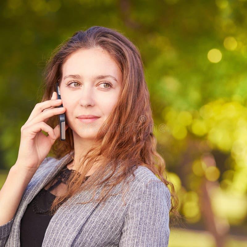 Νέο κορίτσι που χρησιμοποιεί το κινητό τηλέφωνο υπαίθρια Γυναίκα νεολαίας που μιλά όπως το σύμβουλο Επιχείρηση συνομιλίας στοκ εικόνα