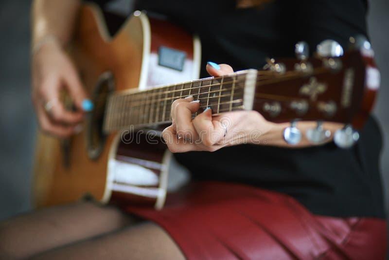 Νέο κορίτσι σε ένα κόκκινο δέρμα miniskirt και το μαύρο pantyhose που παίζει την κιθάρα, κινηματογράφηση σε πρώτο πλάνο, ρηχό βάθ στοκ εικόνες