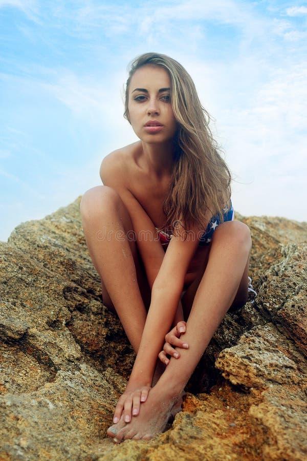 Νέο κορίτσι σε ένα μαγιό στους βράχους κοντά στη θάλασσα στοκ εικόνες