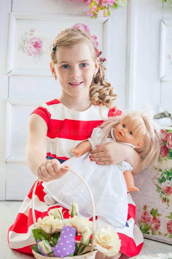 Νέο κορίτσι σε ένα φόρεμα, που παίζει με την κούκλα της στοκ εικόνες