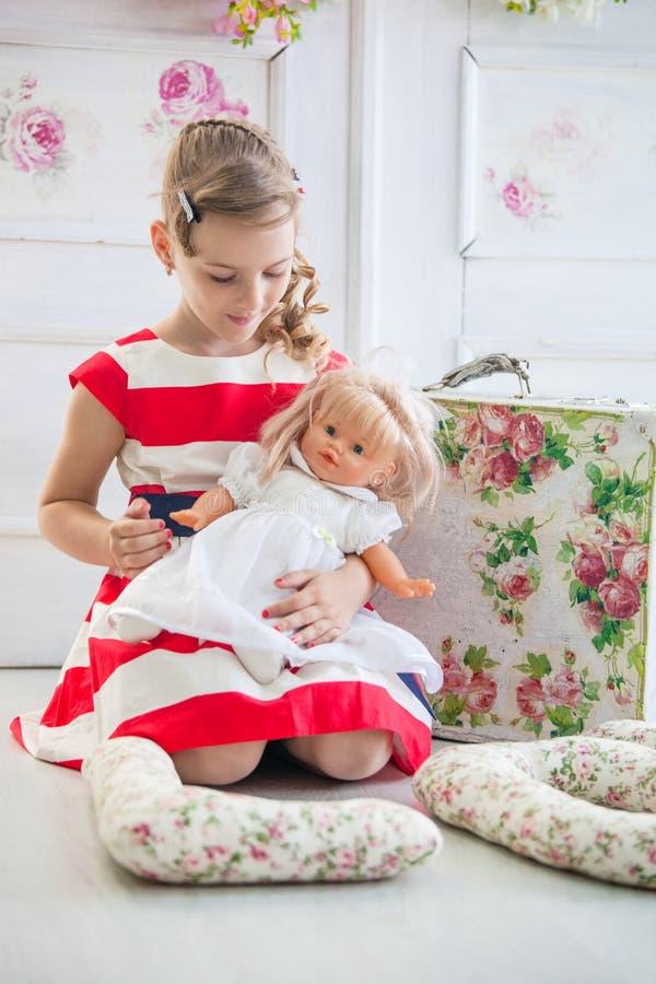 Νέο κορίτσι σε ένα φόρεμα, που παίζει με την κούκλα της στοκ φωτογραφία με δικαίωμα ελεύθερης χρήσης