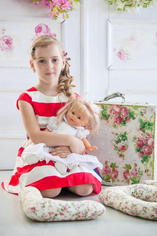 Νέο κορίτσι σε ένα φόρεμα, που παίζει με την κούκλα της στοκ φωτογραφίες με δικαίωμα ελεύθερης χρήσης