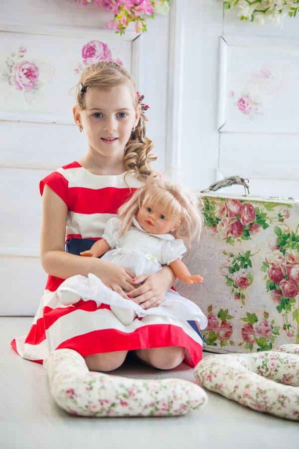 Νέο κορίτσι σε ένα φόρεμα, που παίζει με την κούκλα της στοκ φωτογραφίες