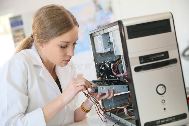 Νέο κορίτσι σπουδαστών που επισκευάζει τον υπολογιστή στοκ φωτογραφίες