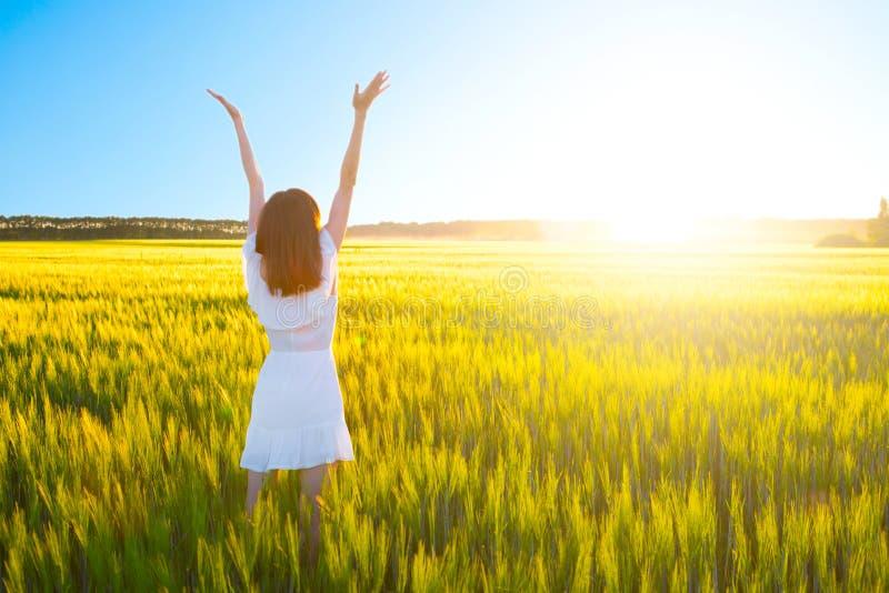 Νέο κορίτσι στα άσπρα χέρια διάδοσης φορεμάτων με τη χαρά και την έμπνευση που αντιμετωπίζουν τον ήλιο στοκ φωτογραφία με δικαίωμα ελεύθερης χρήσης