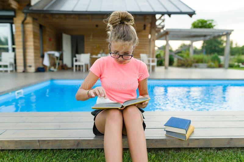 Νέο κορίτσι στα γυαλιά κοντά στη λίμνη με έναν σωρό των βιβλίων, που διαβάζει το βιβλίο Εκπαίδευση, καλοκαίρι, γνώση στοκ φωτογραφία