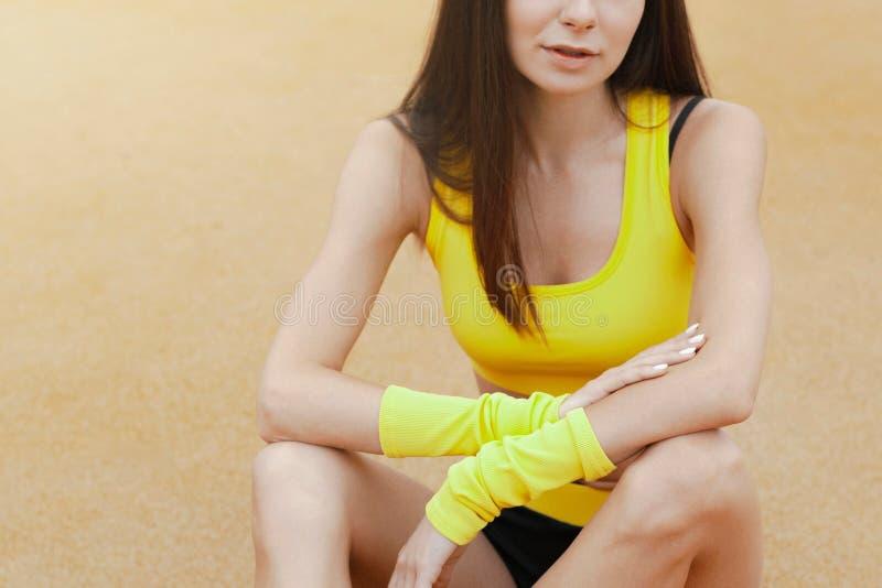 Νέο κορίτσι στην κίτρινη φόρμα γυμναστικής στο έδαφος κατάρτισης στοκ εικόνες