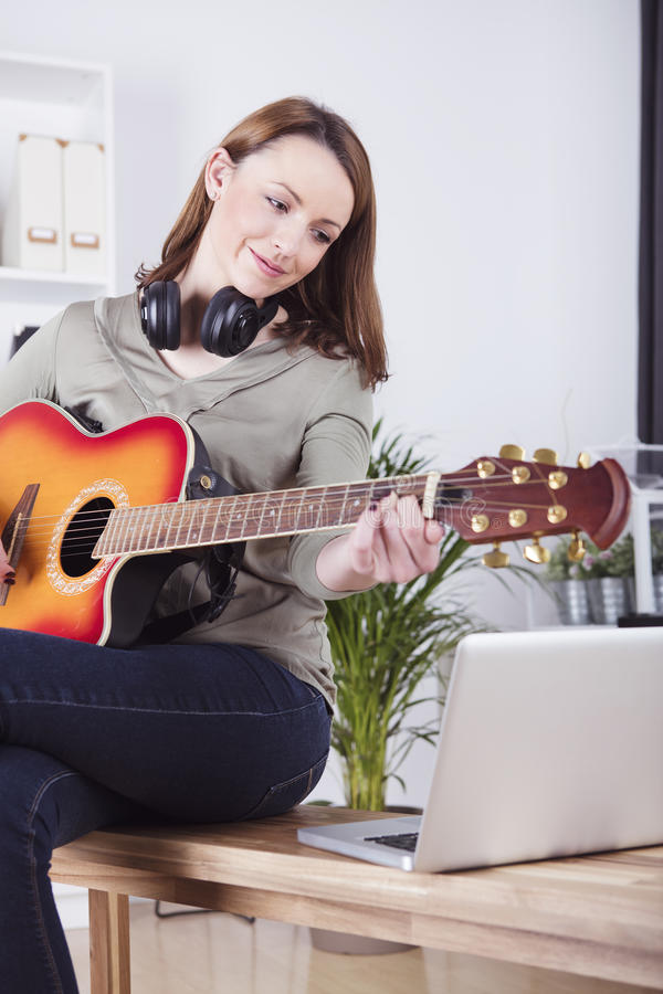 Νέο κορίτσι στην κιθάρα παιχνιδιού καναπέδων στοκ εικόνες