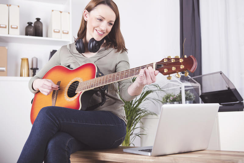 Νέο κορίτσι στην κιθάρα παιχνιδιού καναπέδων στοκ εικόνες με δικαίωμα ελεύθερης χρήσης