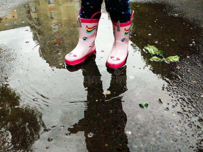 Νέο κορίτσι στις ρόδινες λαστιχένιες μπότες που στέκονται σε μια λακκούβα μετά από μια βροχή υπαίθρια την ημέρα άνοιξη στοκ εικόνες με δικαίωμα ελεύθερης χρήσης