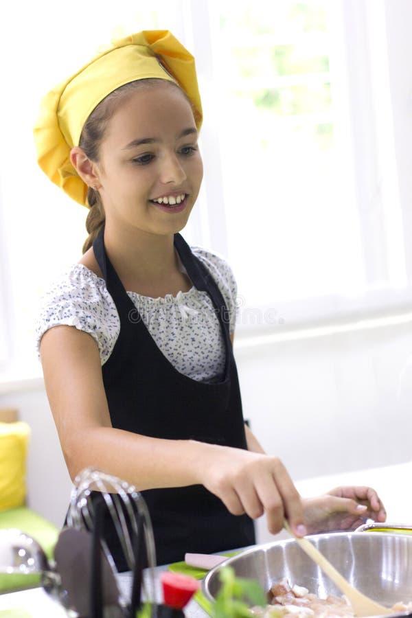 Νέο κορίτσι στους μάγειρες αρχιμαγείρων ` s καπέλων σε μια μεγάλη κατσαρόλλα στο Μαύρο στοκ εικόνα