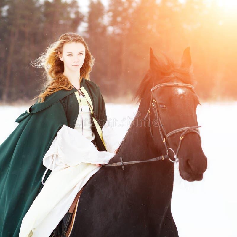 Νέο κορίτσι στο άσπρο άλογο οδήγησης φορεμάτων και ακρωτηρίων στοκ φωτογραφία με δικαίωμα ελεύθερης χρήσης