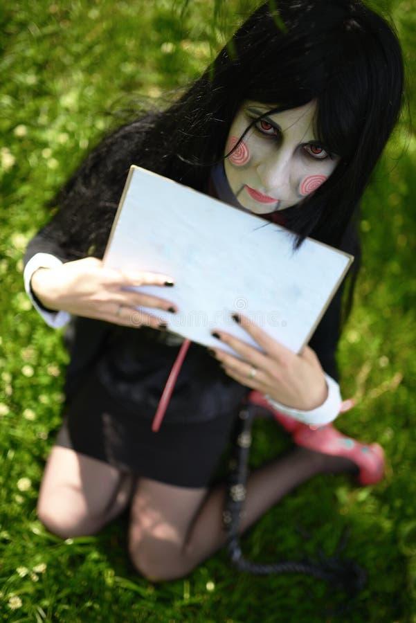 Νέο κορίτσι στο κοστούμι της κούκλας Μπίλι με τα πιάτα cosplay στοκ φωτογραφίες με δικαίωμα ελεύθερης χρήσης