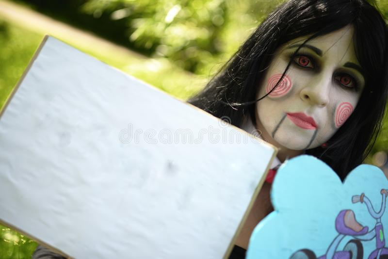 Νέο κορίτσι στο κοστούμι της κούκλας Μπίλι με τα πιάτα cosplay στοκ φωτογραφίες