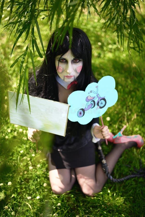 Νέο κορίτσι στο κοστούμι της κούκλας Μπίλι με τα πιάτα cosplay στοκ εικόνες