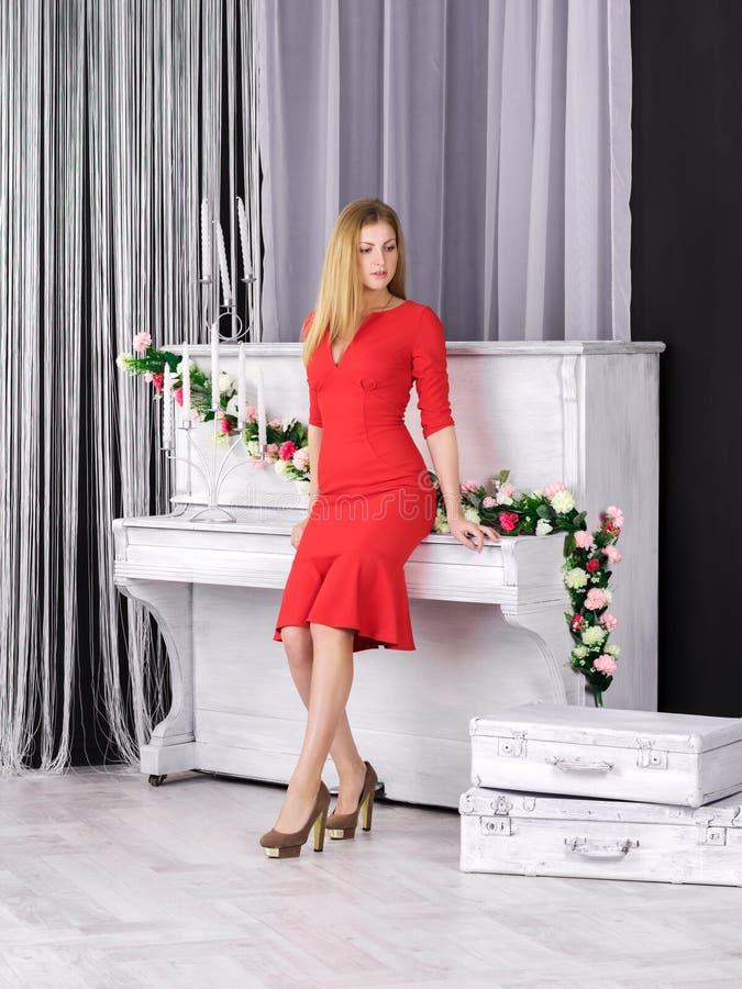 Νέο κορίτσι στο κόκκινο φόρεμα που στέκεται κοντά στο πιάνο στοκ φωτογραφία με δικαίωμα ελεύθερης χρήσης