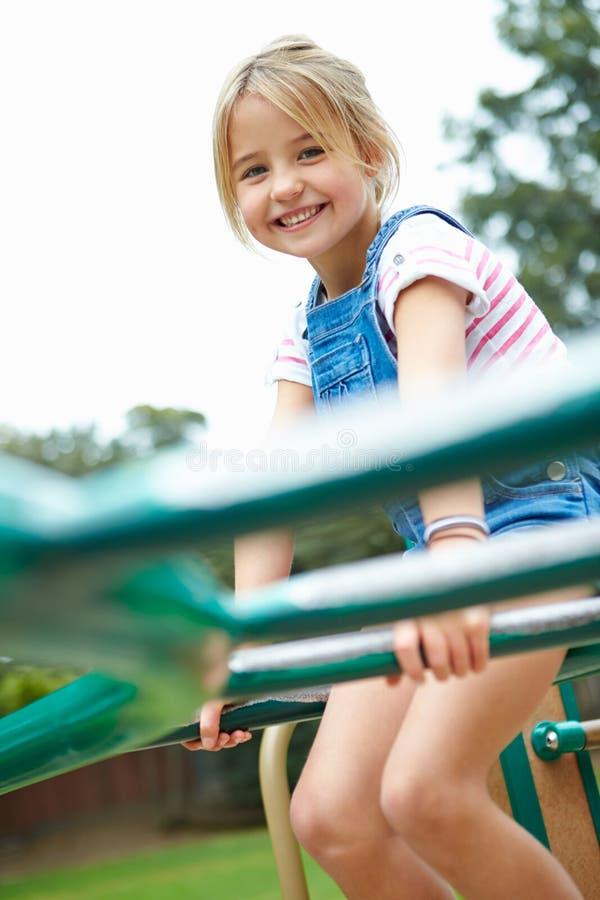 Νέο κορίτσι στο πλαίσιο αναρρίχησης στην παιδική χαρά στοκ φωτογραφίες