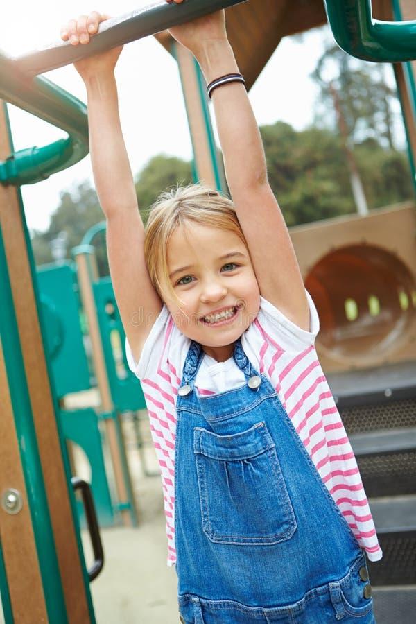 Νέο κορίτσι στο πλαίσιο αναρρίχησης στην παιδική χαρά στοκ φωτογραφία με δικαίωμα ελεύθερης χρήσης
