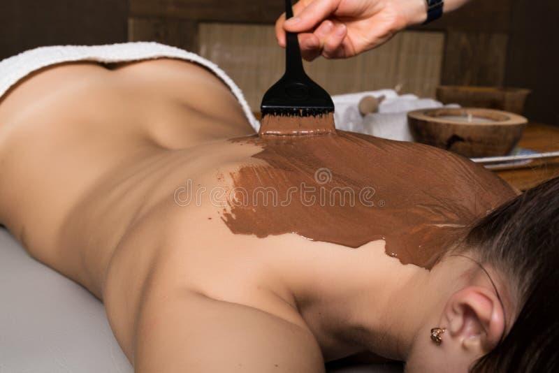 Νέο κορίτσι στο σαλόνι SPA, επεξεργασία περικαλυμμάτων σωμάτων σοκολάτας, αναζωογόνηση δερμάτων Έννοια επεξεργασίας ομορφιάς στοκ εικόνα με δικαίωμα ελεύθερης χρήσης