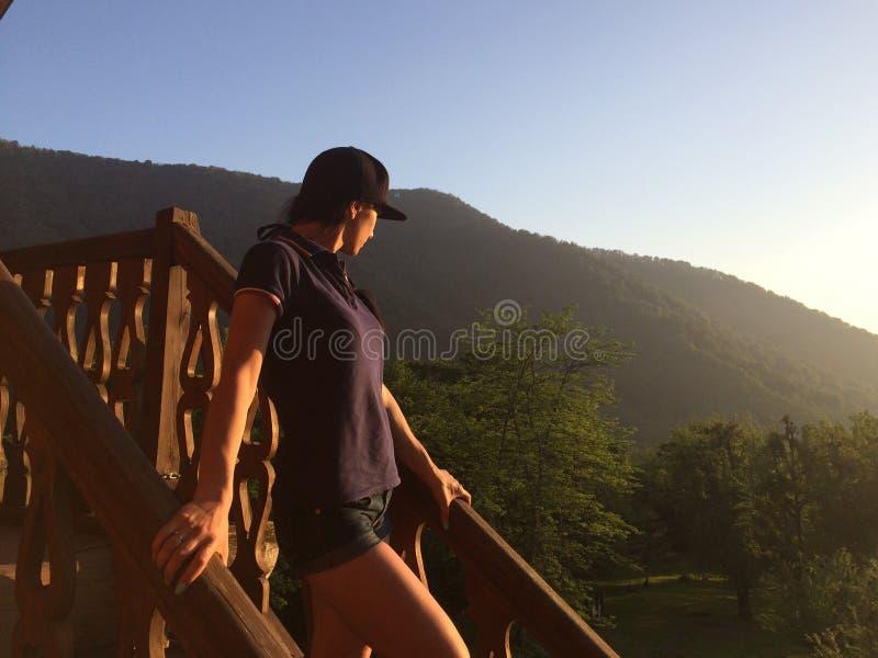 Νέο κορίτσι τουριστών που φορά την ΚΑΠ και τα γυαλιά ηλίου και που φέρνει το σακίδιο πλάτης της, το κατέβασμα ξύλινα και τα σκαλο στοκ εικόνα με δικαίωμα ελεύθερης χρήσης