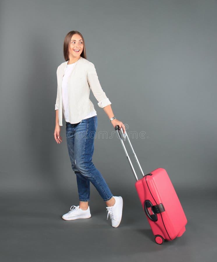 Νέο κορίτσι τουριστών στα θερινά περιστασιακά ενδύματα, με την κόκκινη βαλίτσα, διαβατήριο, εισιτήρια που απομονώνονται στο γκρίζ στοκ φωτογραφία με δικαίωμα ελεύθερης χρήσης