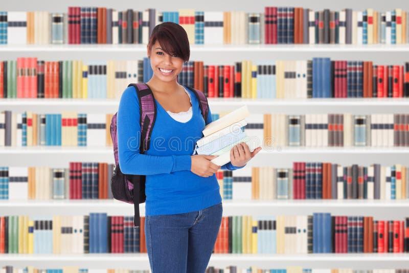 Νέο κορίτσι φοιτητών πανεπιστημίου σε μια βιβλιοθήκη στοκ εικόνες
