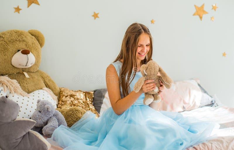 Νέο κορίτσι brunette εφήβων με μακρυμάλλη στην μπλε συνεδρίαση φορεμάτων στο κρεβάτι στην κρεβατοκάμαρά της με τα παιχνίδια στοκ φωτογραφία με δικαίωμα ελεύθερης χρήσης