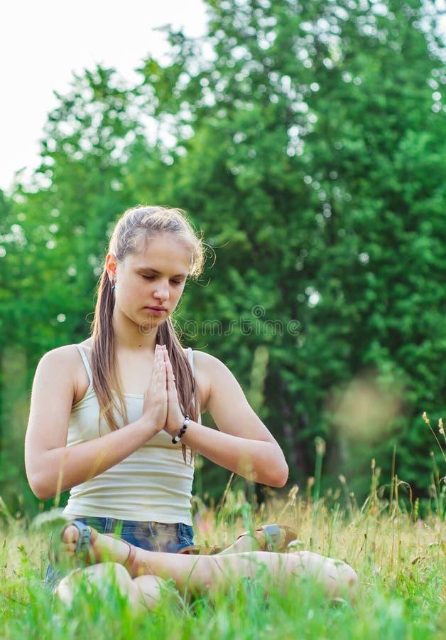 Νέο κορίτσι brunette εφήβων με τη μακρυμάλλη γιόγκα άσκησης στη χλόη στο πάρκο στοκ φωτογραφίες με δικαίωμα ελεύθερης χρήσης