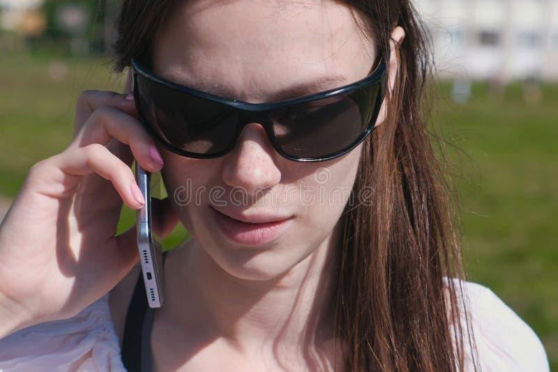 Νέο κορίτσι brunette που περπατά στο πάρκο και που μιλά σε ένα κινητό τηλέφωνο στοκ φωτογραφίες με δικαίωμα ελεύθερης χρήσης