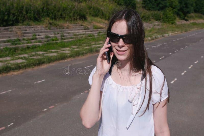 Νέο κορίτσι brunette που περπατά στο στάδιο στο πάρκο και που μιλά σε ένα κινητό τηλέφωνο στοκ φωτογραφίες με δικαίωμα ελεύθερης χρήσης