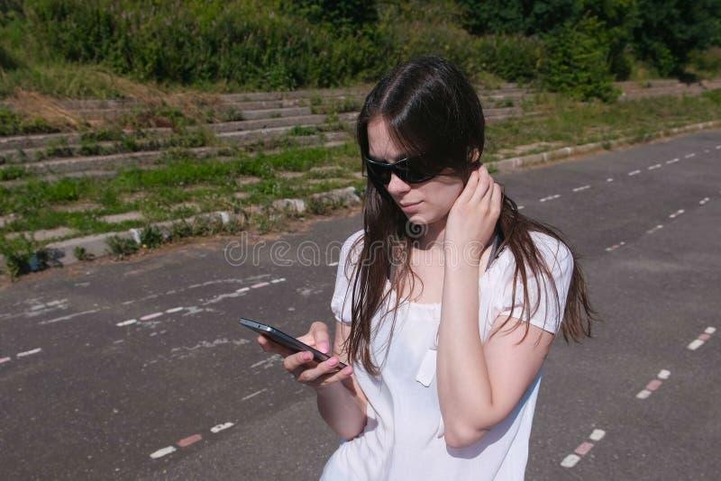 Νέο κορίτσι brunette που περπατά στο στάδιο σε μια κατοικήσιμη περιοχή και ένα μήνυμα σε ένα κινητό τηλέφωνο στοκ εικόνες