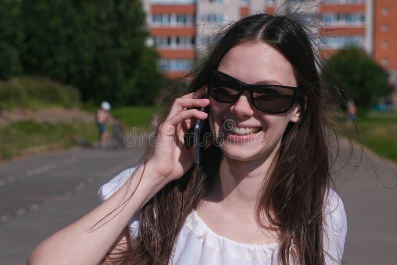 Νέο κορίτσι brunette που περπατά στο στάδιο σε μια κατοικήσιμη περιοχή και που μιλά σε ένα κινητό τηλέφωνο στοκ εικόνα με δικαίωμα ελεύθερης χρήσης