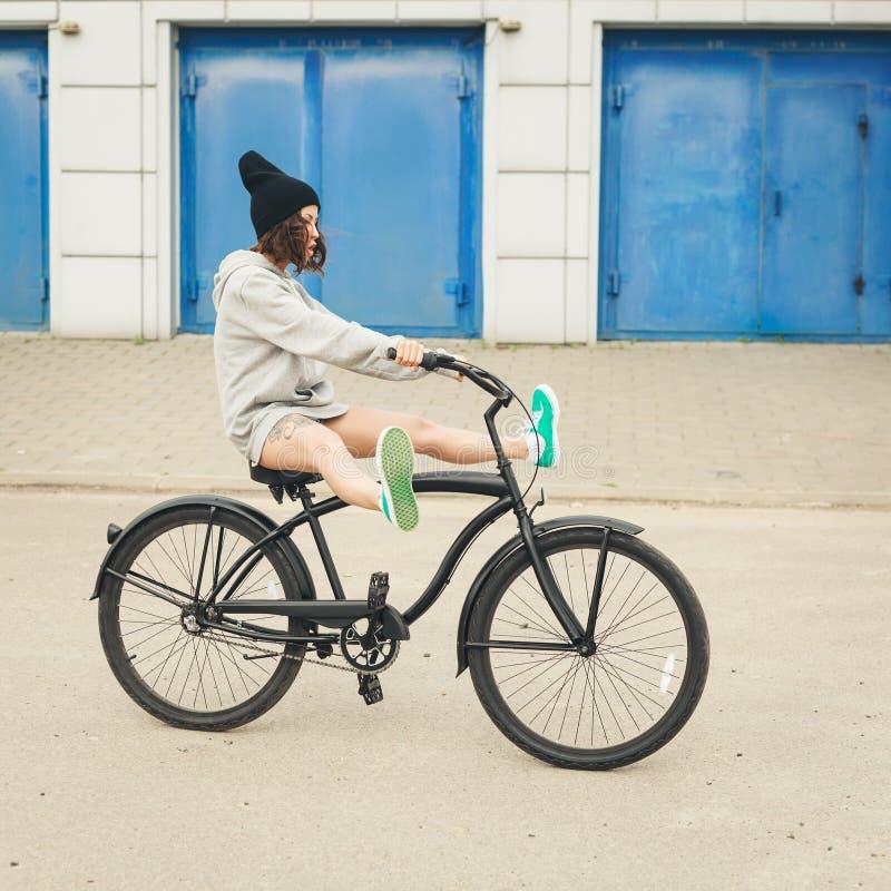 Νέο κορίτσι hipster με το μαύρο ποδήλατο στοκ φωτογραφίες