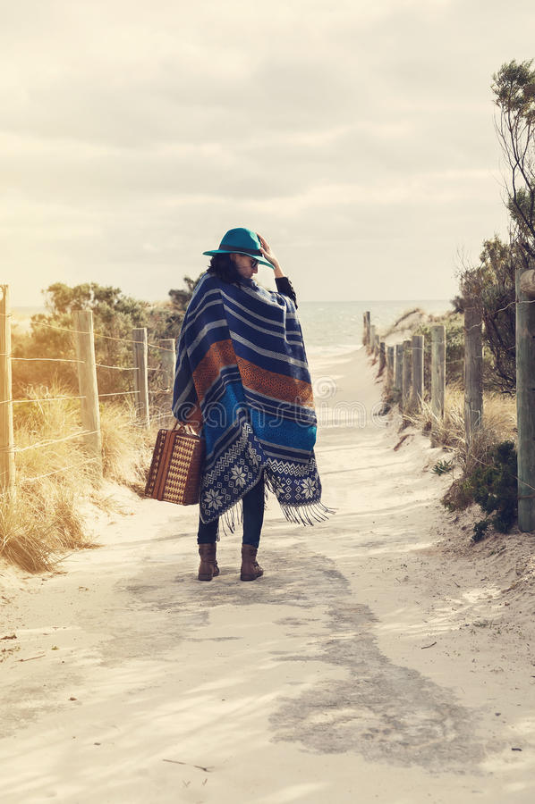 Νέο κορίτσι hipster poncho με την εκλεκτής ποιότητας βαλίτσα στοκ εικόνες