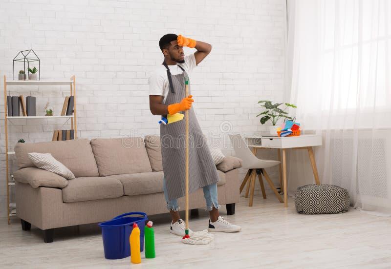 Νέο κουρασμένο καθαρίζοντας εγχώριο πάτωμα ατόμων με τη σφουγγαρίστρα στοκ εικόνες με δικαίωμα ελεύθερης χρήσης