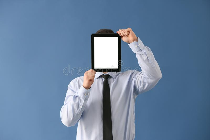 Νέο κρύβοντας πρόσωπο επιχειρηματιών πίσω από τον υπολογιστή ταμπλετών στο υπόβαθρο χρώματος στοκ εικόνες