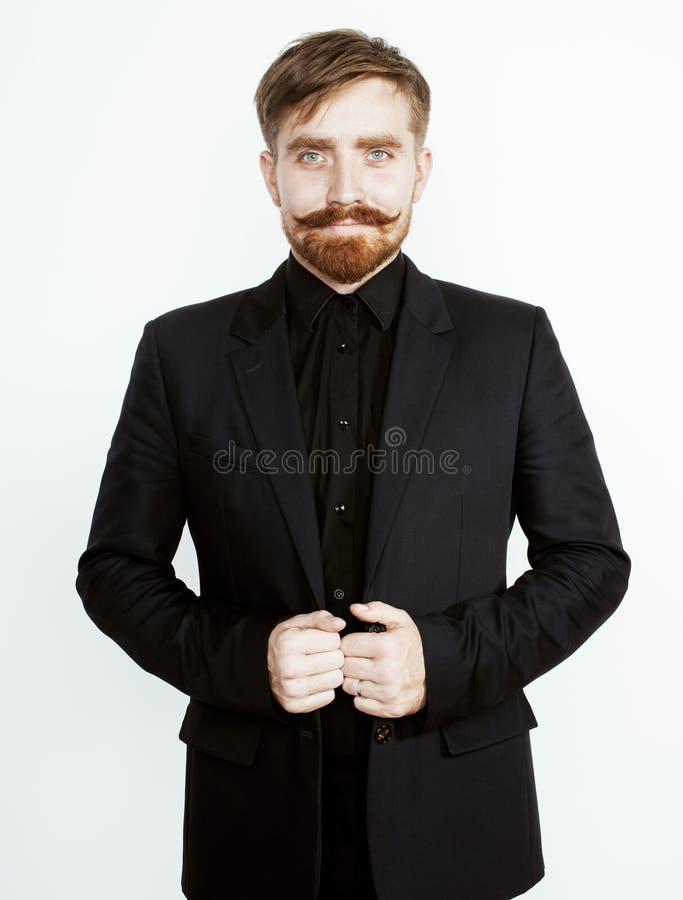 Νέο κόκκινο άτομο τρίχας με τη γενειάδα και mustache στο μαύρο κοστούμι στο άσπρο υπόβαθρο στοκ εικόνες