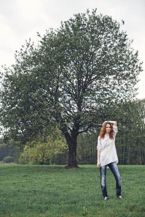 Νέο λατρευτό πορτρέτο γυναικών κοντά στο δέντρο στοκ εικόνα με δικαίωμα ελεύθερης χρήσης