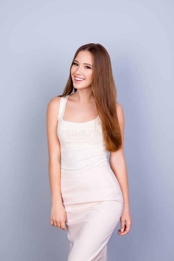 Νέο λεπτό χαριτωμένο κορίτσι στο άσπρο κομψό φόρεμα Είναι επιτυχές α στοκ φωτογραφίες