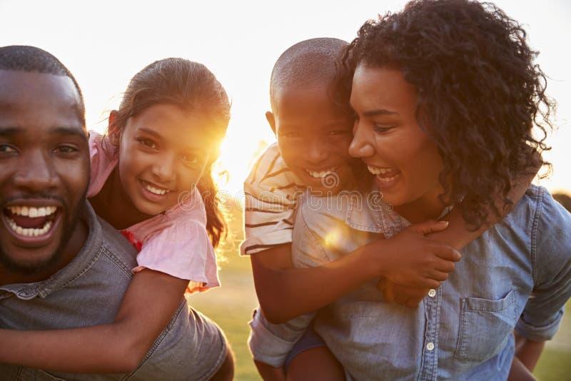 Νέο μαύρο ζεύγος που απολαμβάνει τον οικογενειακό χρόνο με τα παιδιά στοκ εικόνα