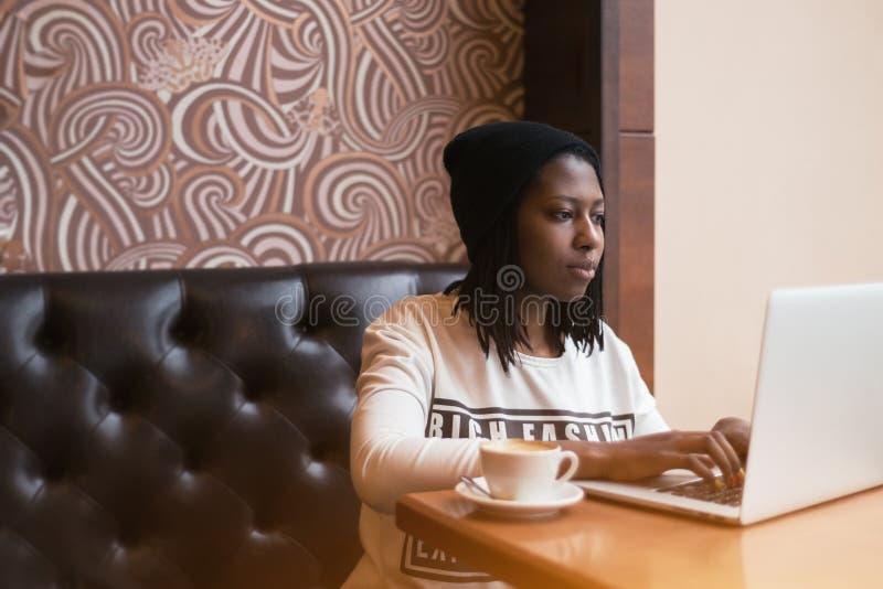 Νέο μαύρο κορίτσι στον καφέ που λειτουργεί στο lap-top στοκ εικόνες με δικαίωμα ελεύθερης χρήσης