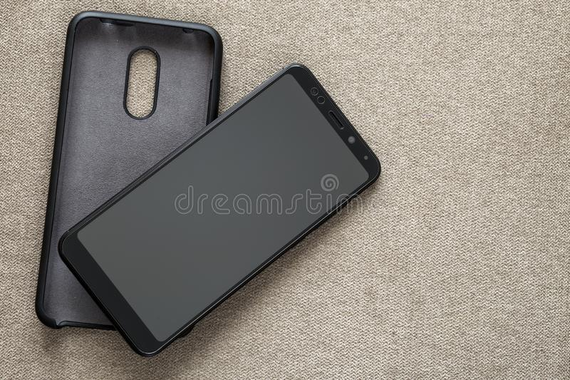Νέο μαύρο σύγχρονο κινητό τηλέφωνο και πλαστική προστατευτική περίπτωση που απομονώνονται στο ελαφρύ διαστημικό υπόβαθρο αντιγράφ στοκ φωτογραφία με δικαίωμα ελεύθερης χρήσης