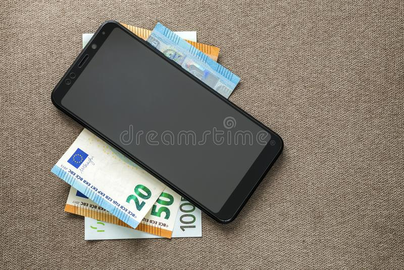 Νέο μαύρο σύγχρονο ψηφιακό κινητό τηλέφωνο στα ευρο- τραπεζογραμμάτια χρημάτων στο διαστημικό υπόβαθρο σύστασης αντιγράφων Σύγχρο στοκ εικόνες με δικαίωμα ελεύθερης χρήσης