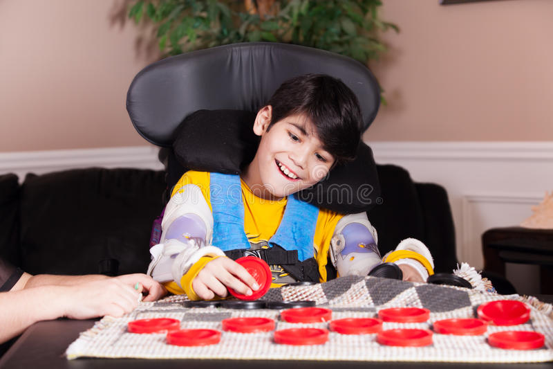 Νέο με ειδικές ανάγκες αγόρι στην αναπηρική καρέκλα παίζοντας ελεγκτές στοκ εικόνες