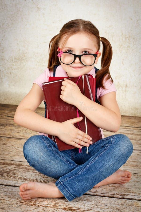 Νέο μικρό κορίτσι που φορά τα γυαλιά που κάθονται στο πάτωμα και που κρατούν τα βιβλία στοκ φωτογραφία