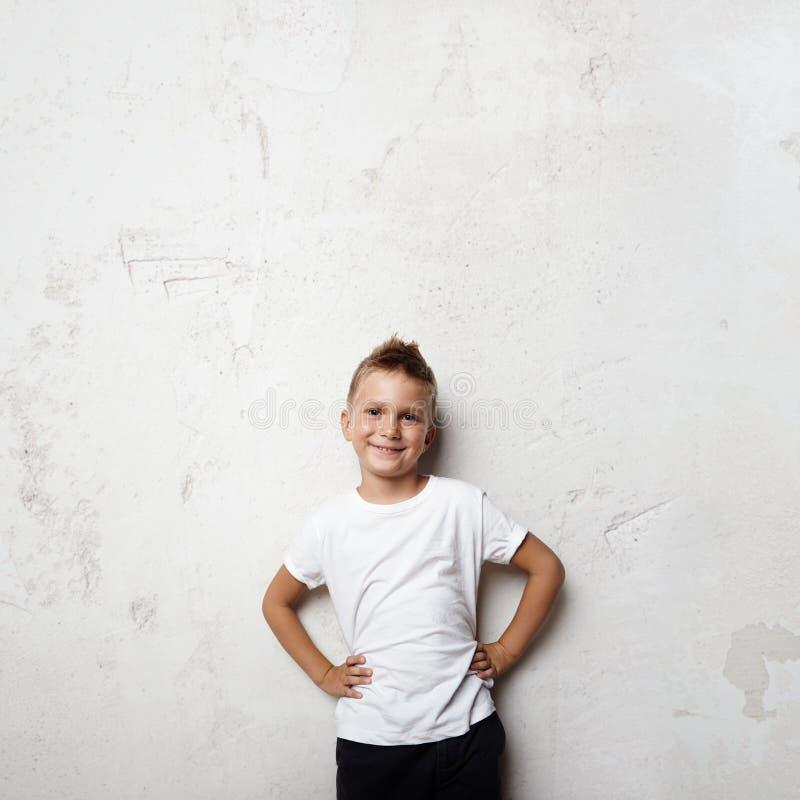 Νέο μικρό παιδί που φορά την άσπρη μπλούζα και το χαμόγελο στοκ εικόνα